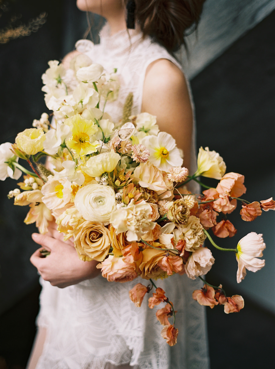 bride holding a white yellow and orange ombre wedding bouquet