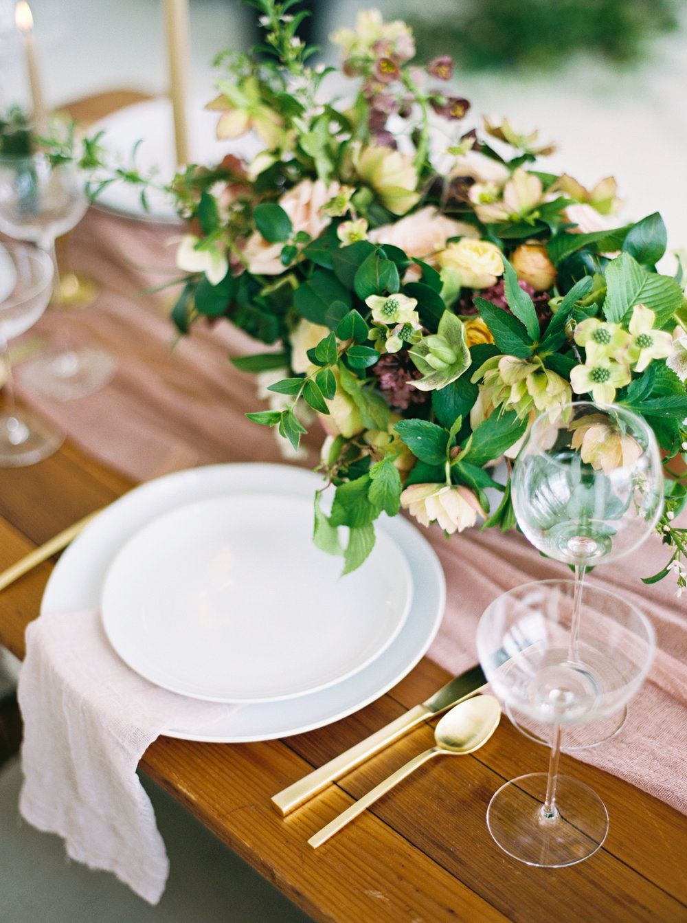 minimalist wedding table with white plates gold flatware and a green spring bouquet