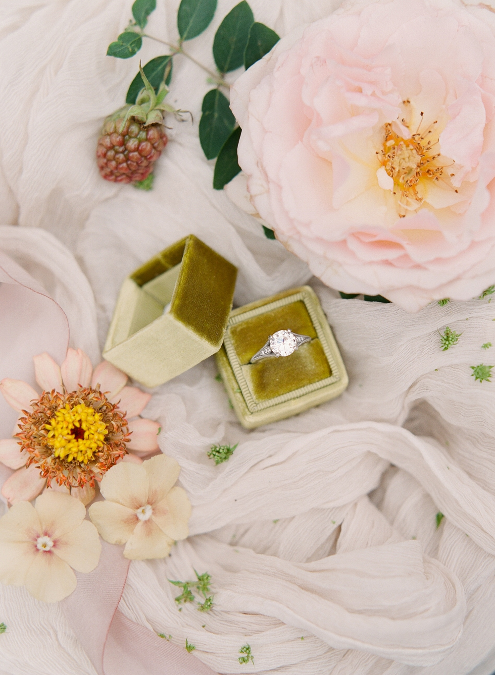 diamond engagement ring in mustard yellow velvet ring box surrounded by pink flowers and berries