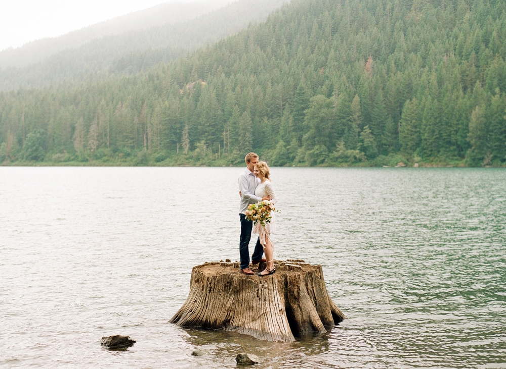 couple standing on tree stump in rattlesnake lake