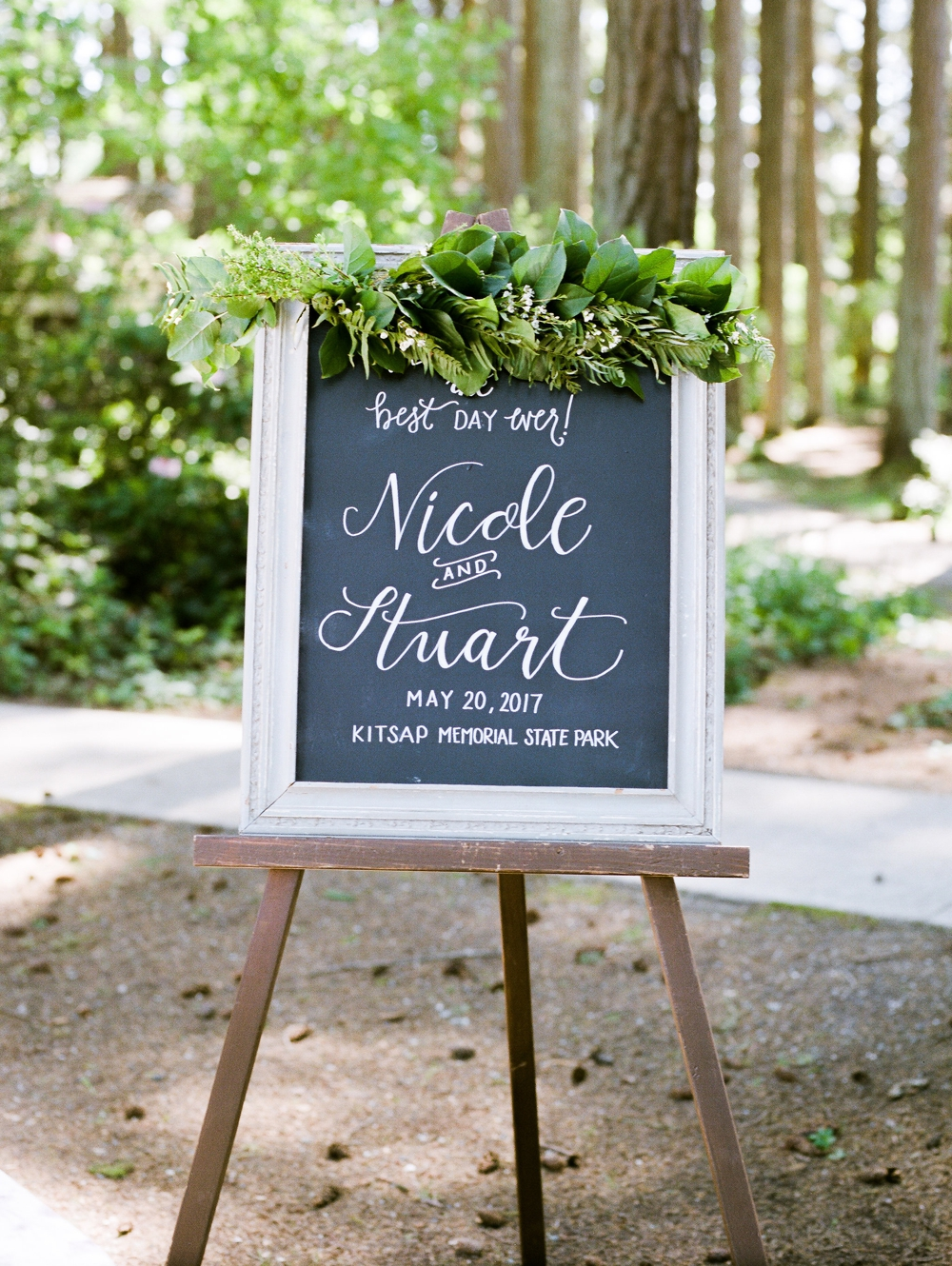 wedding welcome chalkboard with green foliage