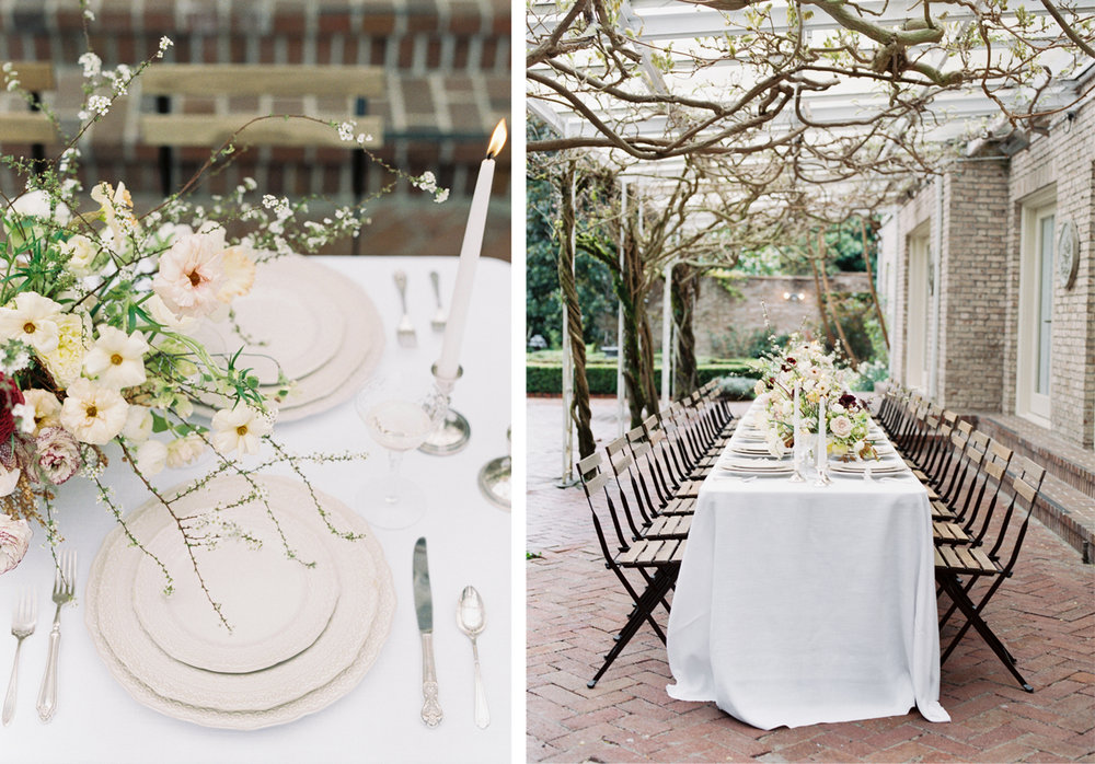 white flowers with woody vines hanging over white plates and a long table under a grape vine pergola