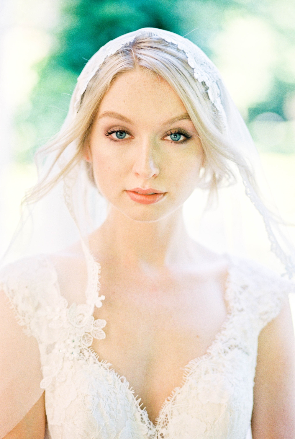 blonde bride with lace veil and dress gazing directly at the camera