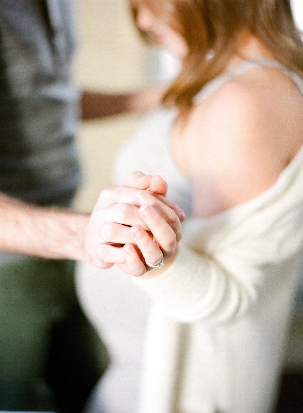 man and pregnant woman in white sweater holding hands