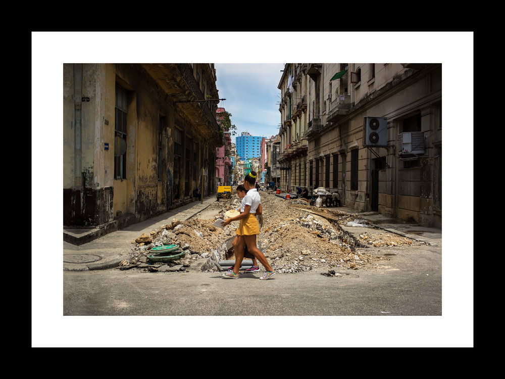 juxtaposition with school girls | © preston lewis thomas | $550 In the foreground we have two young girls on their way to school. In the background, we have a scene from Inception. This pretty much sums up the visual nature of Havana. the skirts worn by the young girls in this photograph don't start out that way. When the uniform first arrives, the skirt actually stops just below the knees. But as every parent knows... teenagers are gonna be teenagers, and that's that.