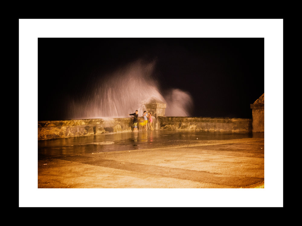 the Water Dance on the Malecón | © preston lewis thomas | $575 Evening on the Malecón. As we walked along I noticed these children huddled in the corner, giggling and excited. I stopped to see what this was all about. Woosh! The Atlantic slammed against the breakwall then rained down in a deluge. Screams and laughter filled the night air as they danced back and forth. I parked myself on the pavement, adjusted my camera and waited... giggling and excited.
