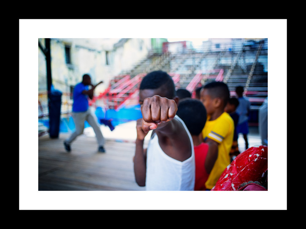 The young Boxer | © preston lewis thomas | $575 SPending an afternoon at gymnasio de boxero san raphael trejo, havana. this young man, the boxer was ever intense and focused. destined for greatness, I believe. he always knew where my camera was. in the middle of a boxing drill, he gave me this gift.