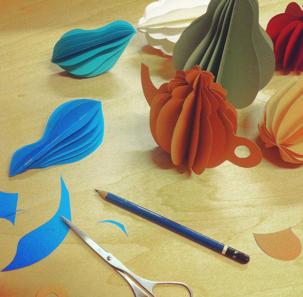 新しい形はいつも『手』で考える。作品を作る時、机の上はいつも紙の試作でいっぱいになっていた。