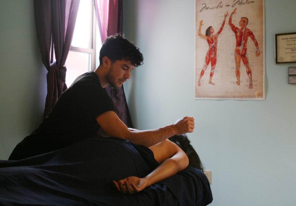 Photo credit:  Spinney . [Image description: Gabriel using a deep tissue massage technique on a client.]