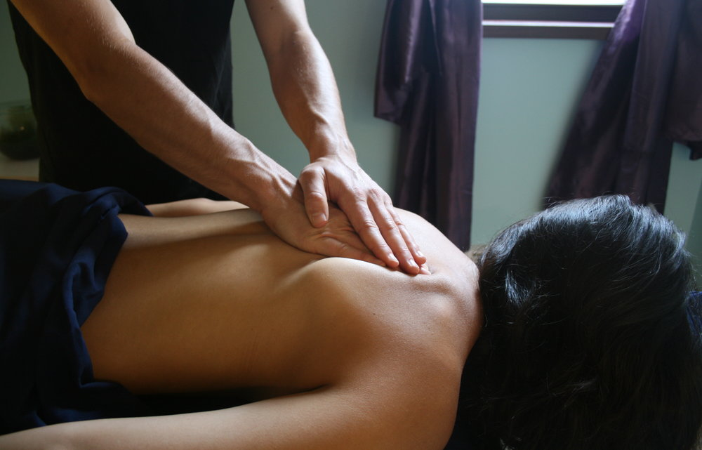 Photo credit:  Spinney . [Image description: Photo of Gabriel massaging a client's upper back.]