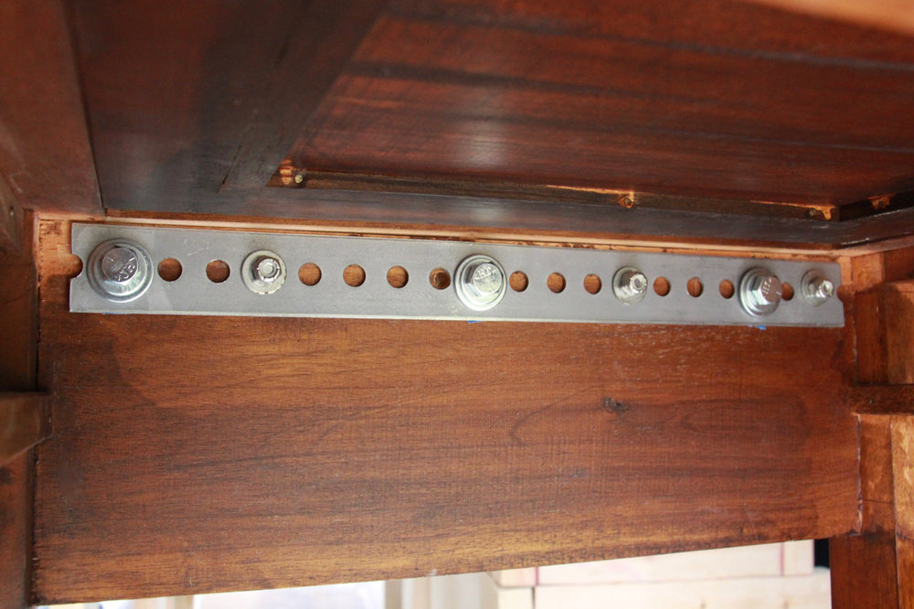 """This view shows the front side of the roll top desk, from below:  only visible after removing the main drawer. There was a little play after screwing in the 3/8"""" bolts fully into the L-track, which we fixed by adding extra washers under the bolt heads on this side."""