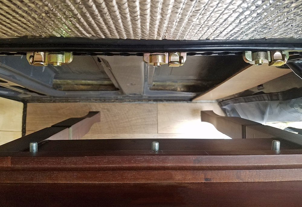 """Overhead view of the roll top desk, being tipped away from the van wall. The camera lens distorts the perspective a little bit, but you can see the three 3/8"""" bolts protruding from the back of the desk and where they mate into the L-track fittings."""