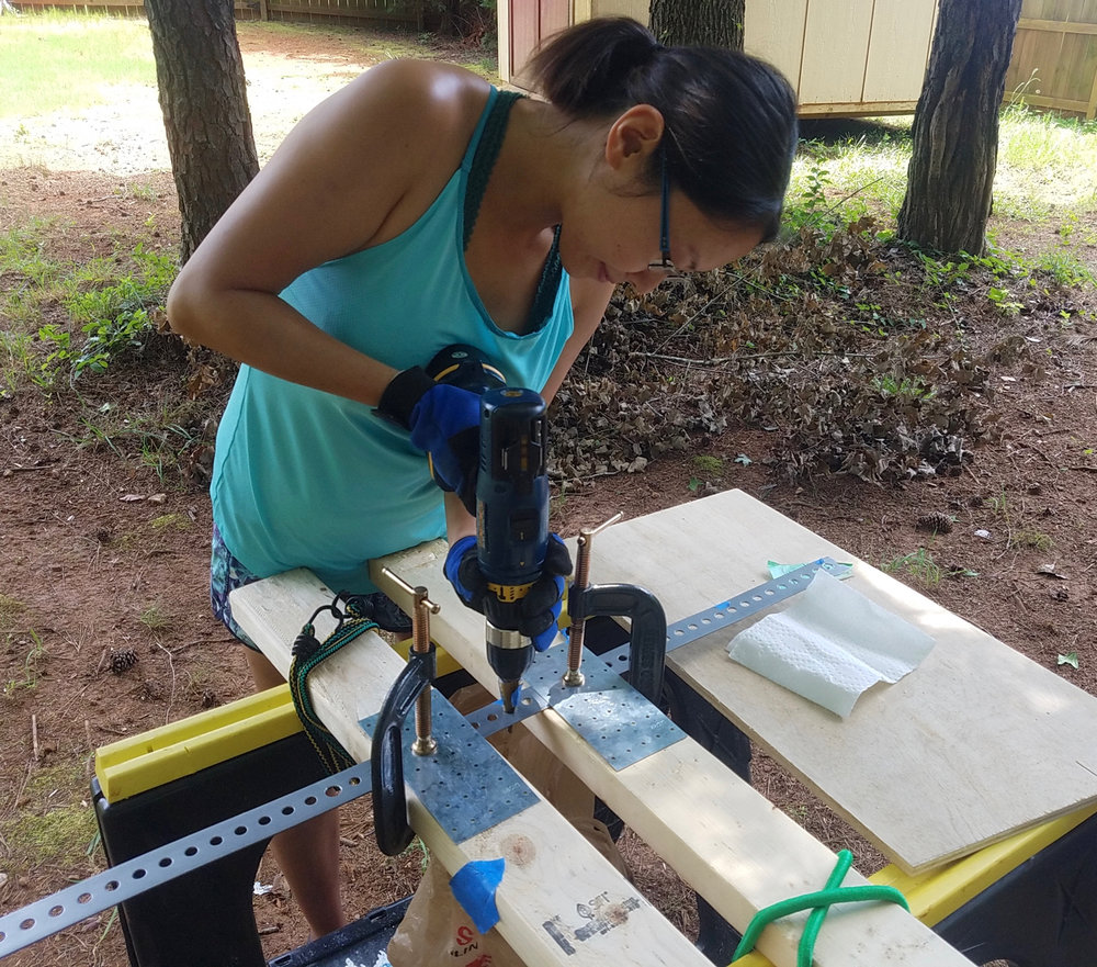 Shelly rocking the step drill, widening a few pre-punched holes on our DIY furniture bracket.