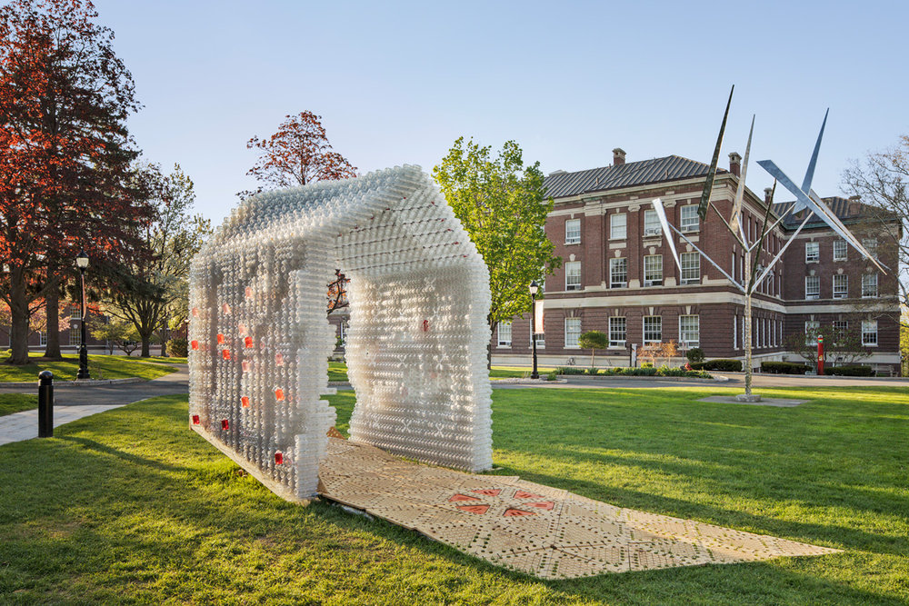 """- The pavilion was for an experimental study of using plastic bottles as shelter for disaster relief purposes. Custom 3D printed joints and cross bracing help securing the structure along the interlocking bottles that are joined together to """"construct"""" the walls.read more"""