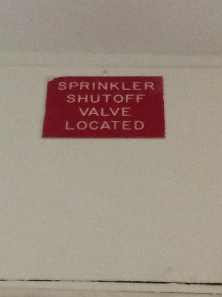 The purpose of this sign is to signal the location for where the sprinkler shutoff valve is. In my perspective, the sign is not finished as it is.