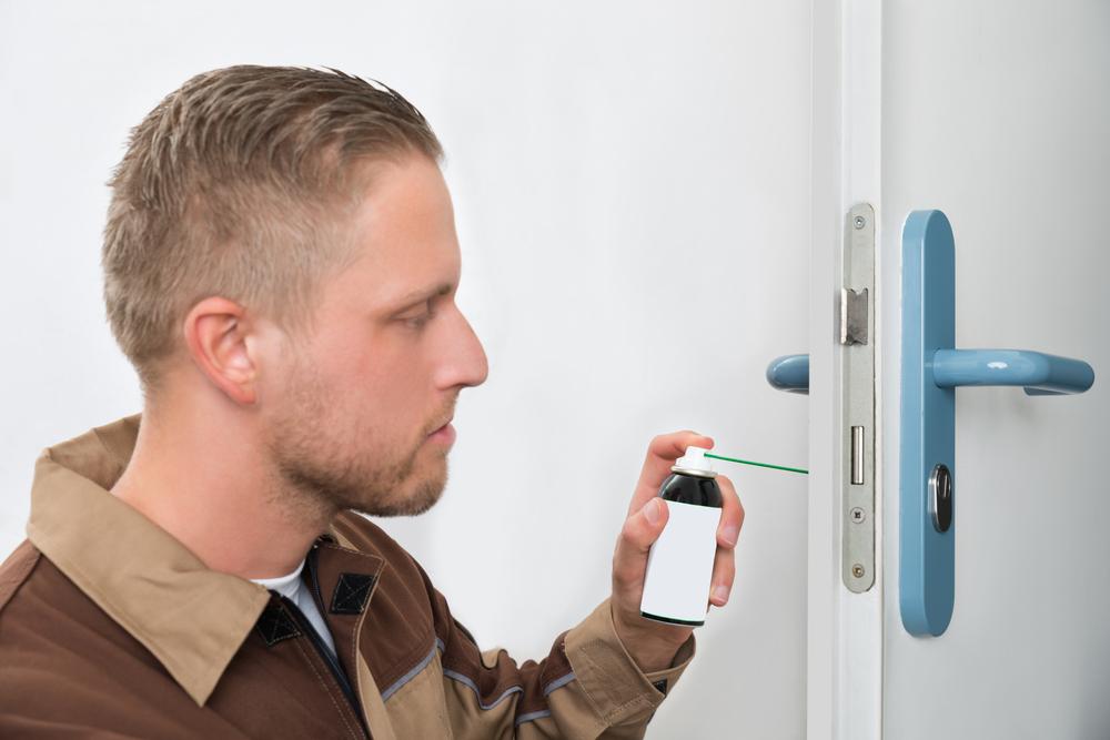 young man lubricating door locks