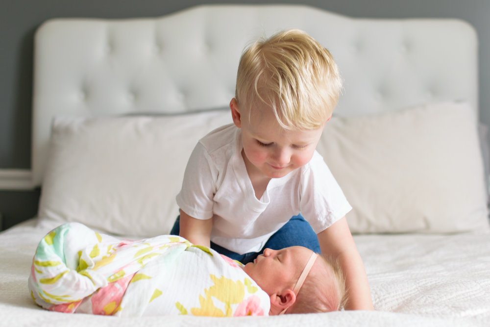 this is an image of a toddler boy and his baby sister newborn laying on the bed. the toddler boy is looking at her baby newborn sister sleeping.
