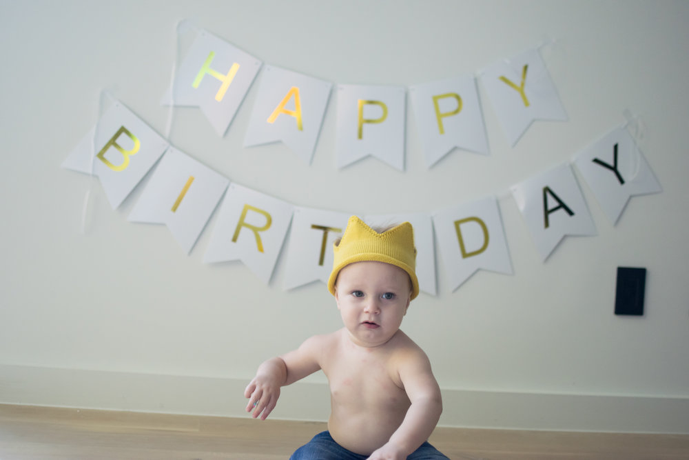 this is an image of a toddler child boy sitting on the floor, in front of a happy birthday sign, with his fingers in his birthday cake
