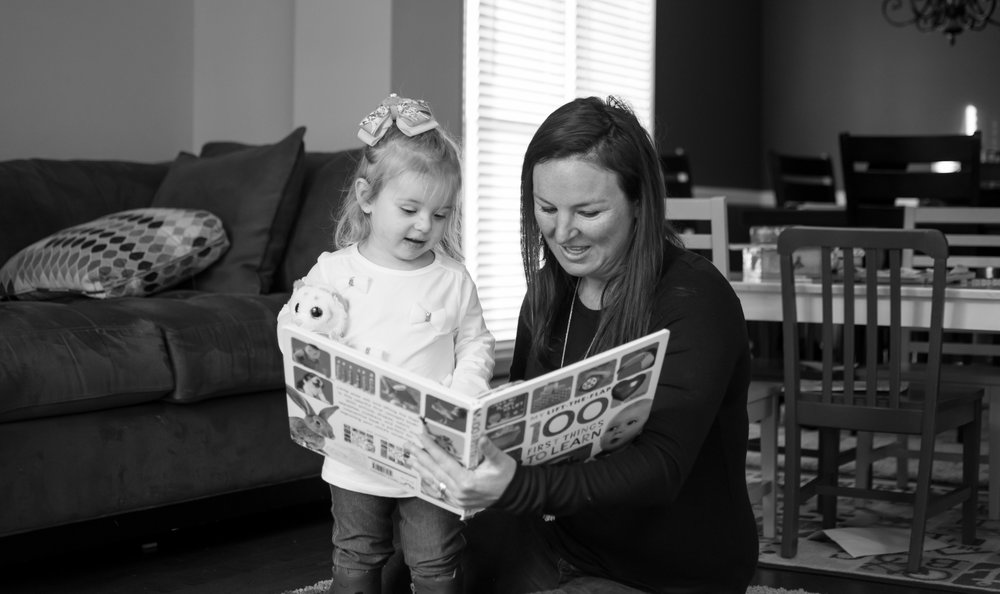 this is a black and white image of a mother sitting down and reading a book to a young little girl