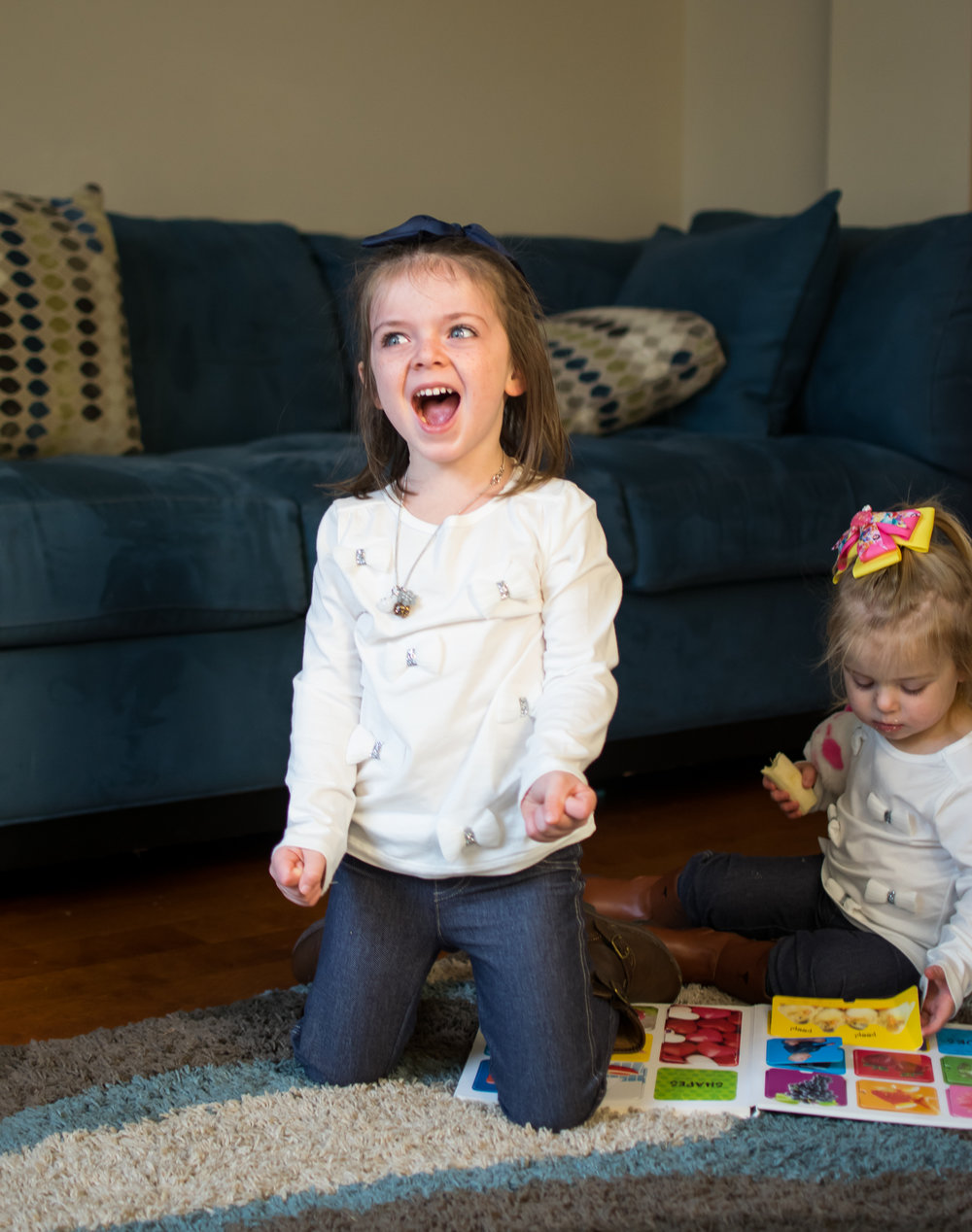 this is an image of two little girl sisters in the living room, one is looking at a book, and the other girl is laughing and looking at mom