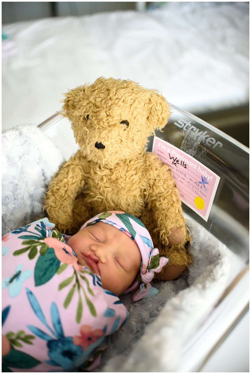 this is an image of a newborn baby girl laying in a hospital bassinet. she is sleeping and there is a family teddy bear next to her in the bassinet.