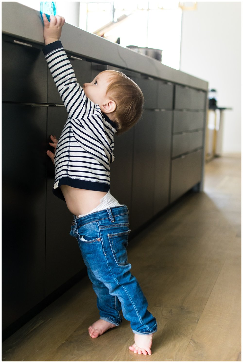 this is an image of a young child standing on his tippy toes trying to reach for his cup. the image was taken during an in home lifestyle session in atlanta georgia.