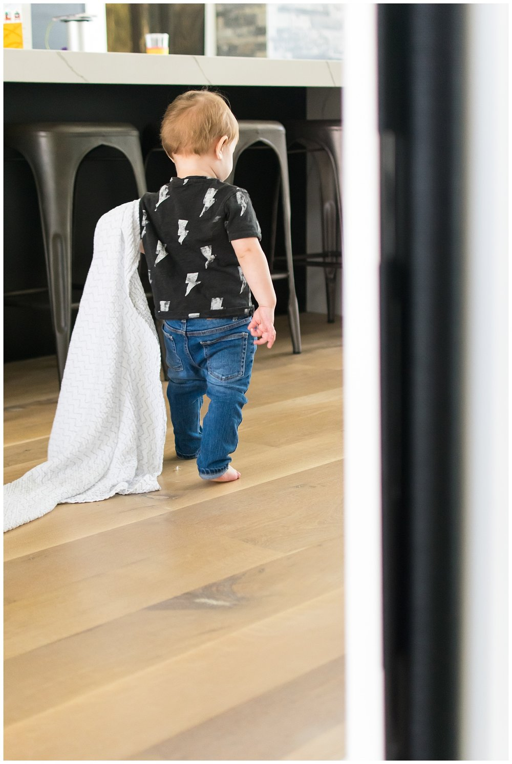 this is an image of a toddler boy walking and holding onto his blanket. the image was taken during an in home lifestyle session in atlanta georgia.