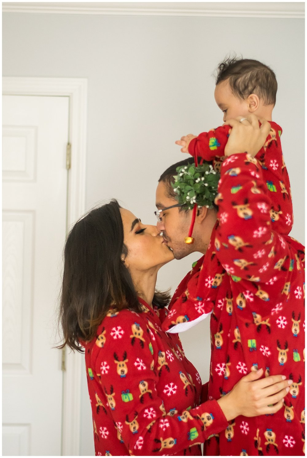 this is an image of a family in matching christmas pajamas. dad is holding the six month boy on his shoulders and mom and dad are under the mistletoe that the baby is holding