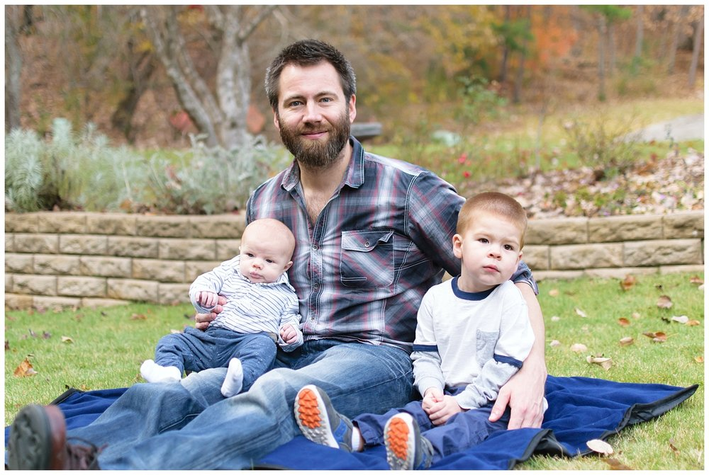 this is an image of the boys of the family during a lifestyle family session in marietta georgia. the image contains the father and the two young boys.