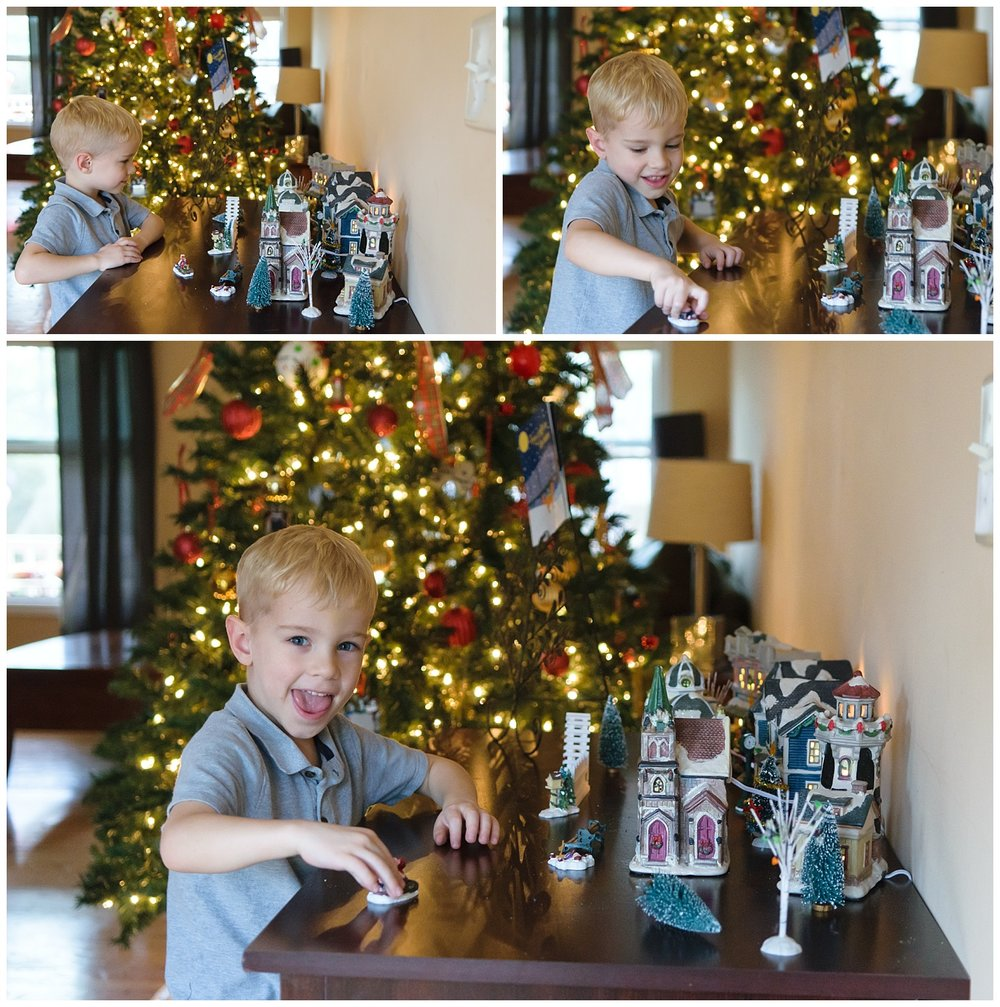 these are images of a young boy looking at the family's christmas village ornaments. the images were taken indoors during a lifestyle family session in lilburn, georgia.