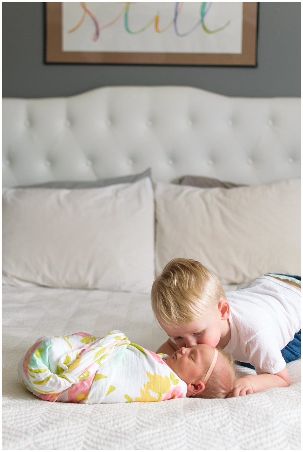 this image was taken during a lifestyle newborn family session. the baby girl is laying on the bed and her brother is kissing her cheek.