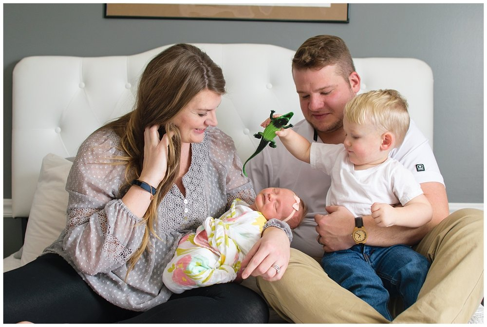 this is a lifestyle image of a family sitting on the  bed during a lifestyle newborn family session.