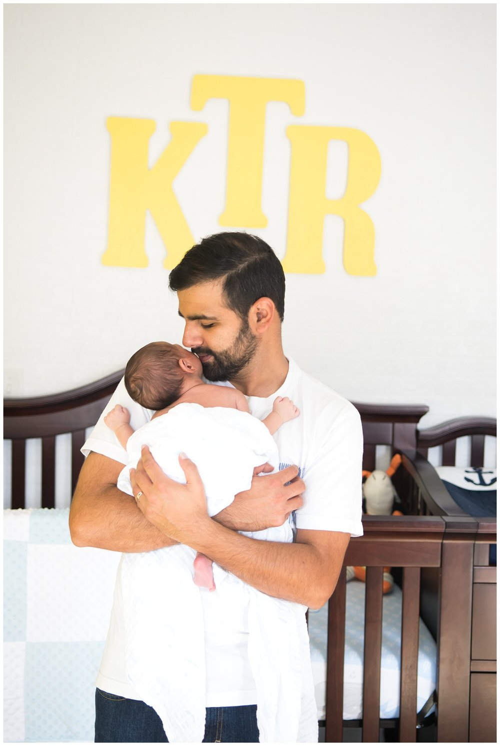 this is an image of a father holding his newborn baby boy and standing in front of the baby's crib. the session took place in decatur georgia