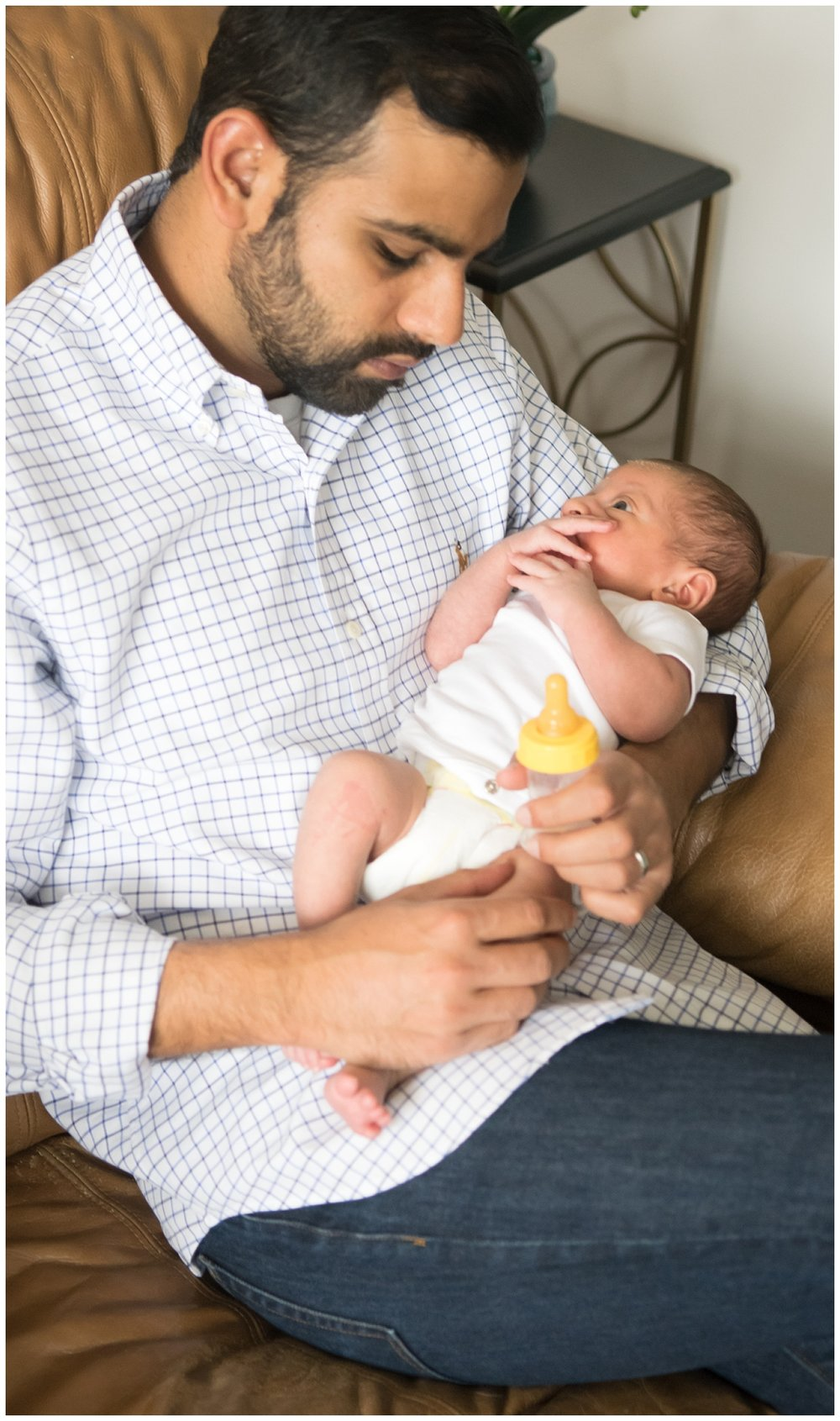 this is a candid image of a dad holding his newborn son while sitting on the couch. this was taken during a lifestyle newborn family session in decatur georgia.
