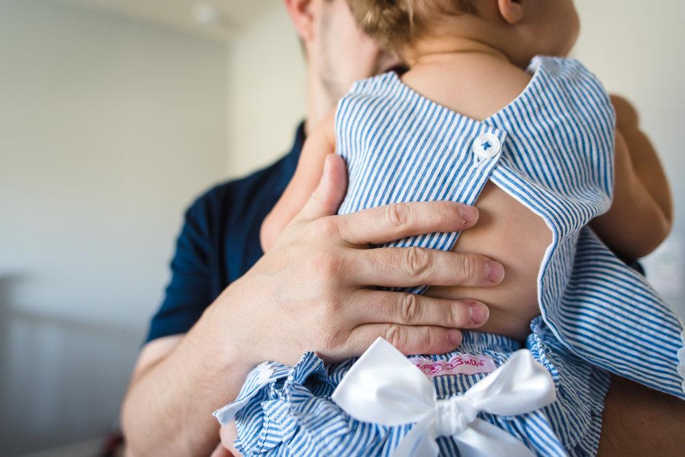 dads-hand-back-of-toddler-blue-dress