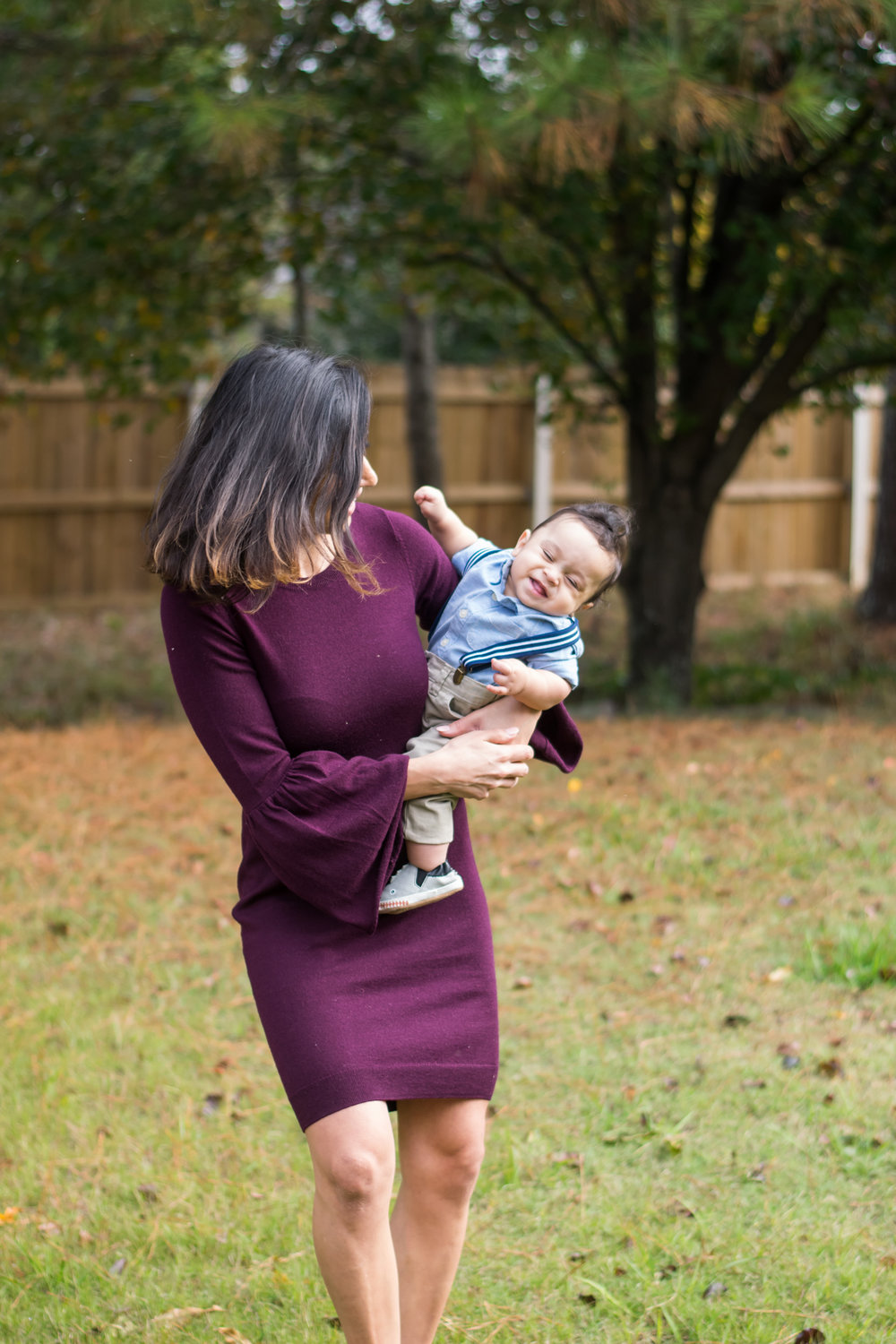 mom-holding-baby-boy-while-laughing-outdoor-family-session