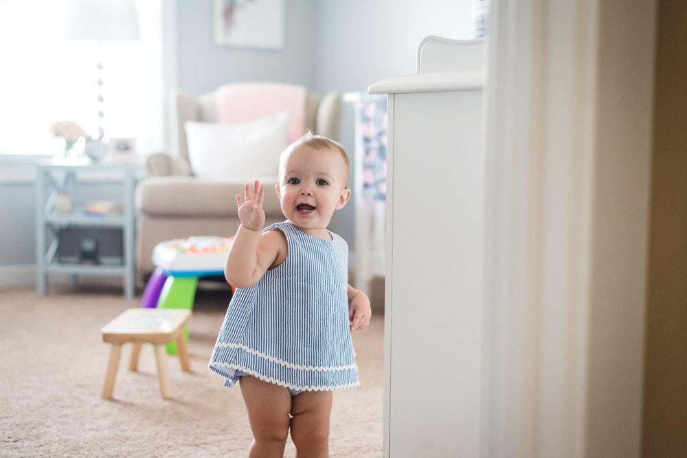 toddler-in-room-waving-at-camera