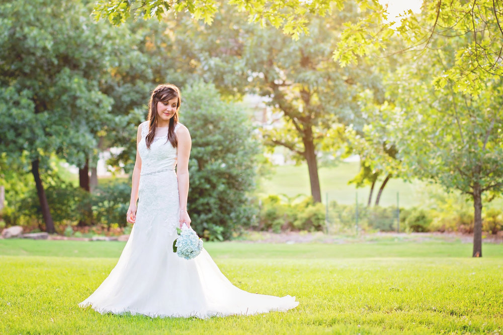 bride holding flowers standing in open park in tulsa oklahoma