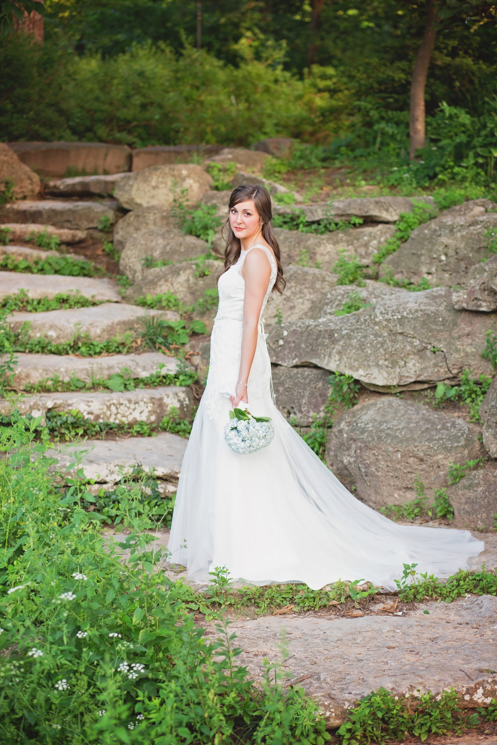 bride holding flowers standing on rock stair case in tulsa oklahoma