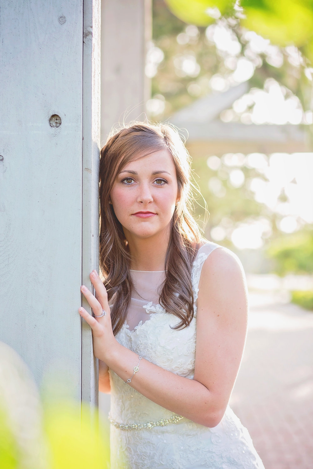 bride leaning against wooden pole in park in tulsa oklahoma