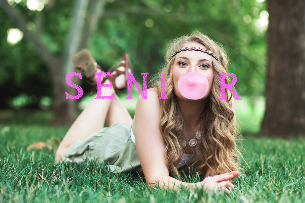 senior girl blowing pink bubble with the word senior written around her in pink.