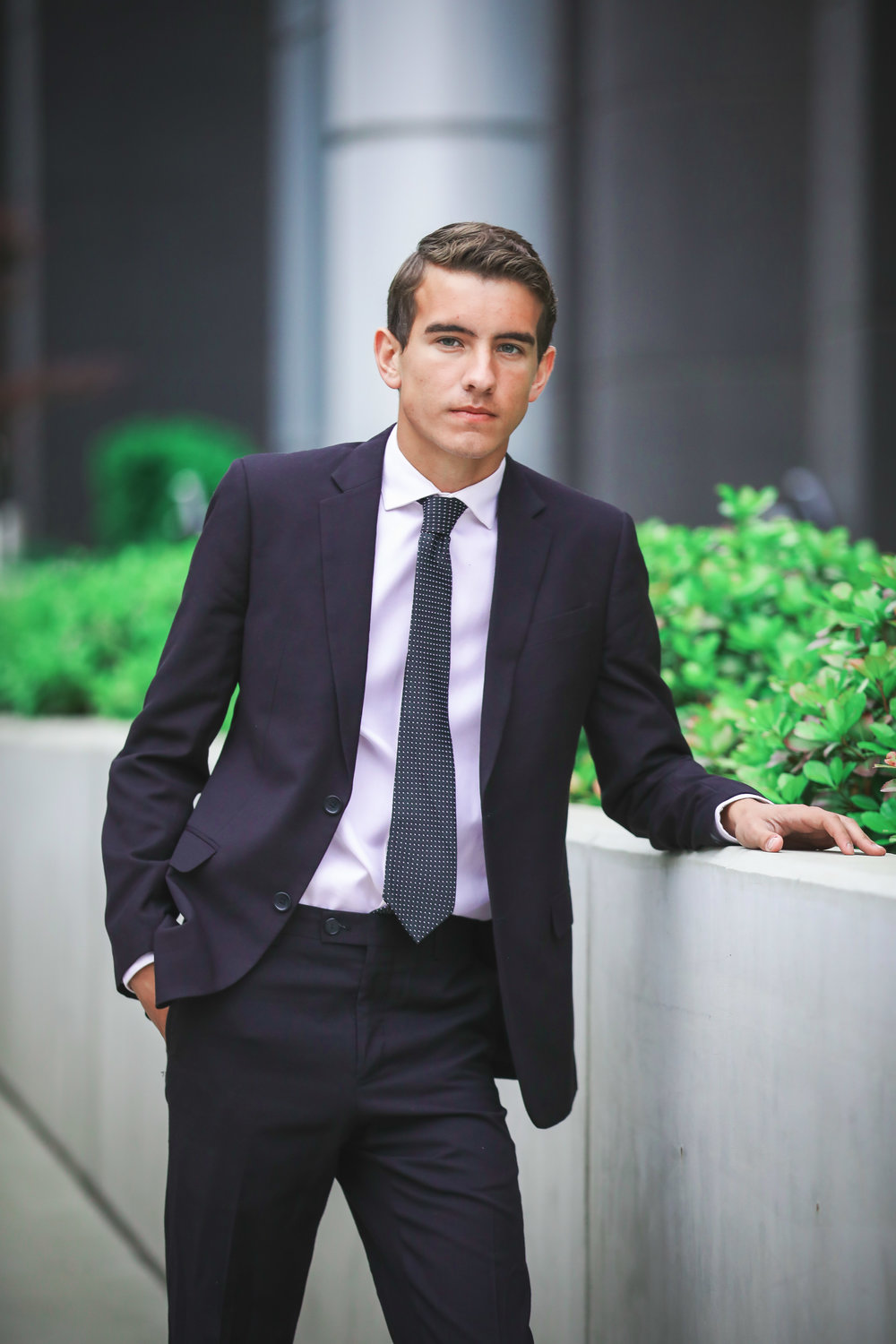 high school senior boy wearing black suit and tie, leaning on concrete wall in downtown oklahoma city