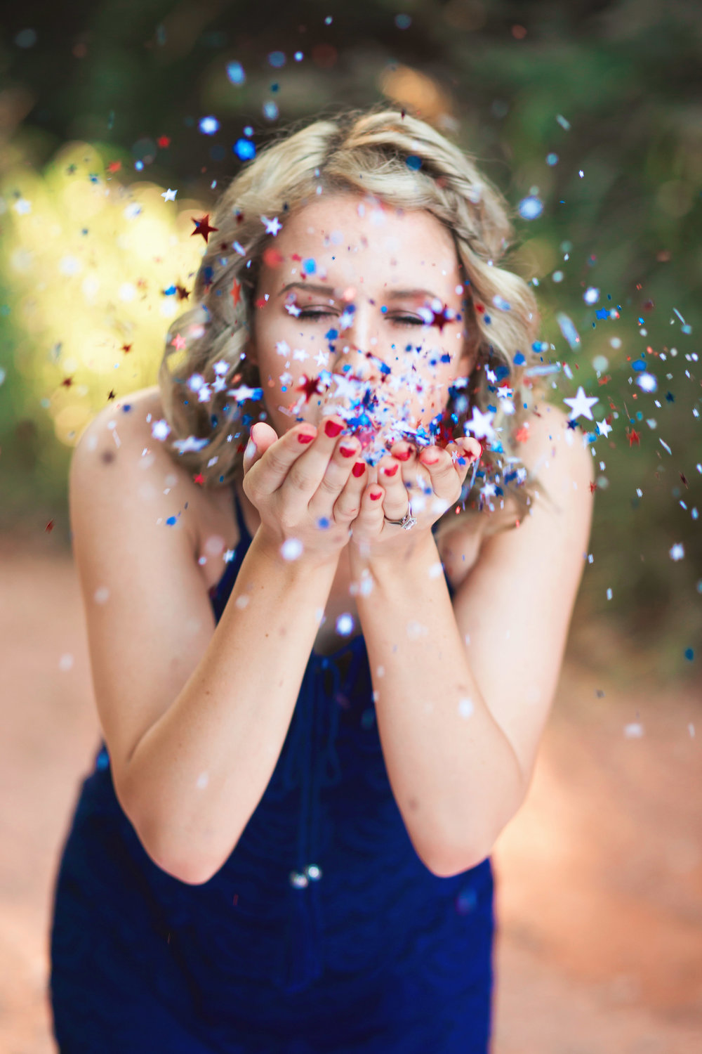 senior girl wearing blue dress blowing star shaped confetti out of her hands