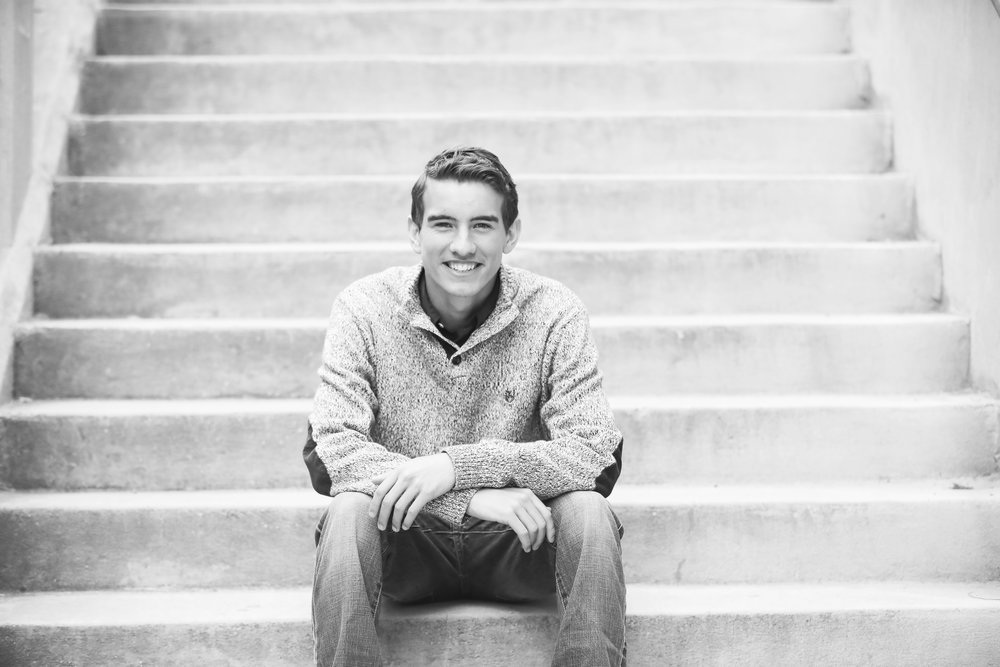 black and white of senior boy sitting on step in downtown oklahoma city
