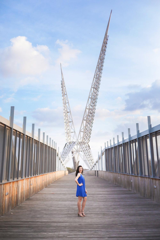 senior girl wearing blue dress standing on the skydance bridge in oklahoma city