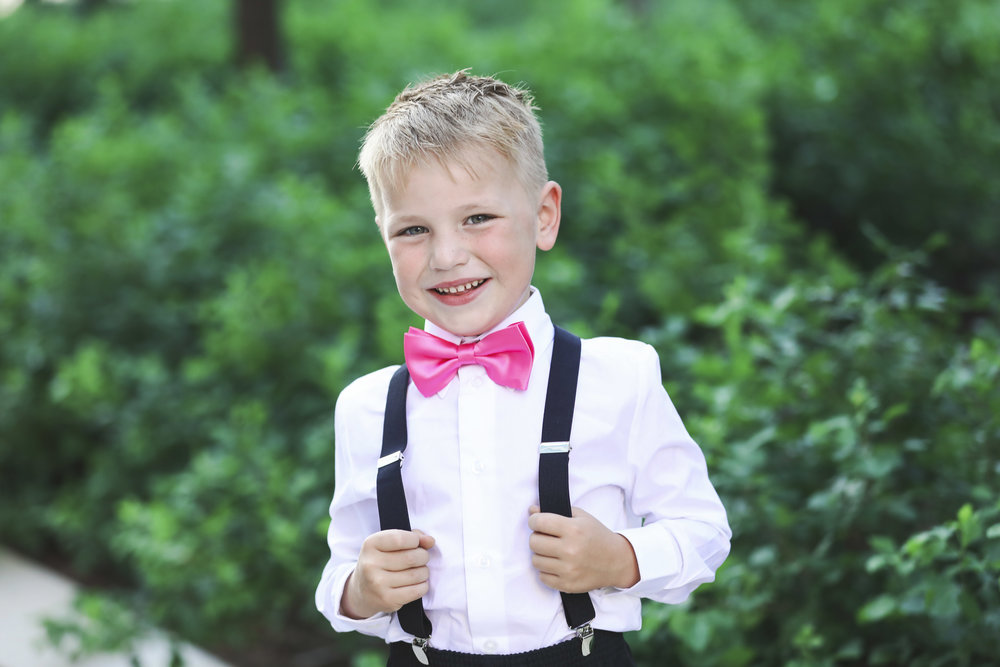 little boy wearing pink bow tie and suspenders smiling at camera in downtown oklahoma city