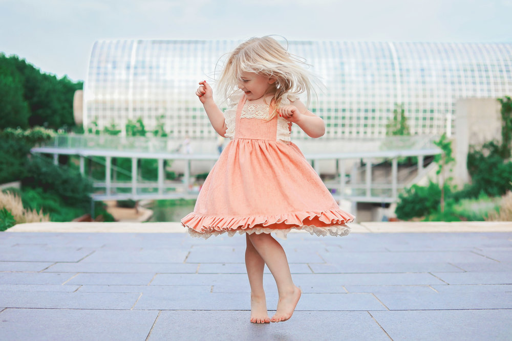 little girl wearing peach colored dress dancing in front of myriad gardens in oklahoma city