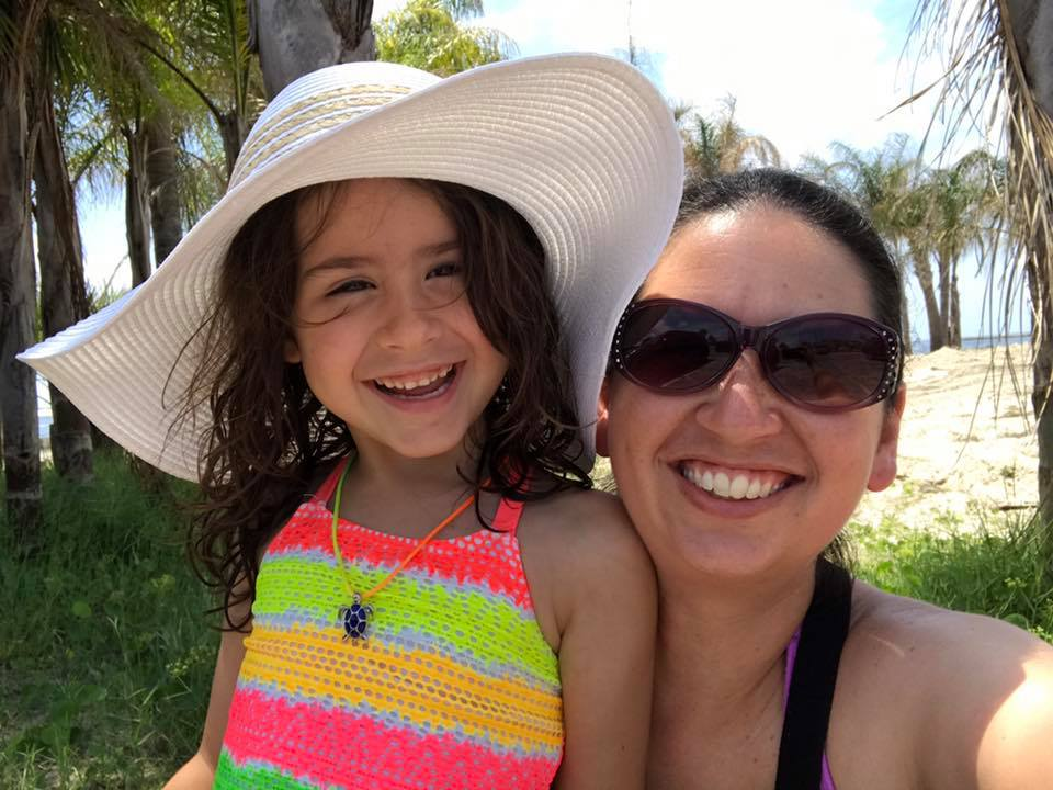 selfie of mother and daughter on the beach with palm trees in the background