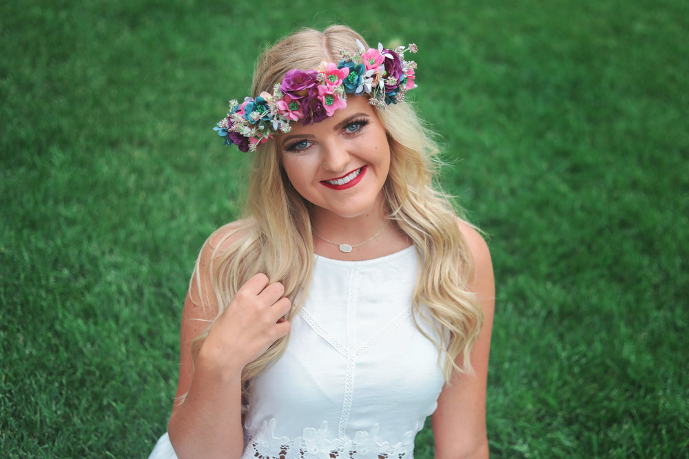 Oklahoma high school senior girl wearing flower head dress and white dress sitting on grass at Myriad Gardens in Oklahoma City.