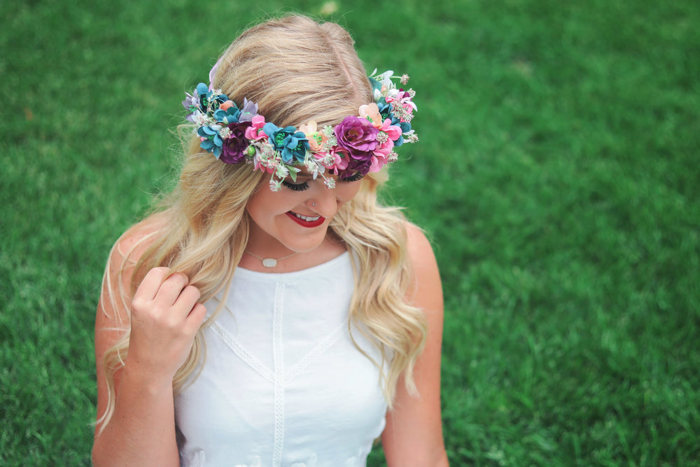 Oklahoma high school senior girl wearing white dress and flowers on her head laughing and looking down
